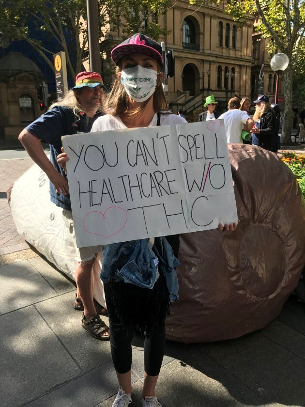 A protester stands across the road from NSW parliament on Tuesday to demand better access to medical cannabis.