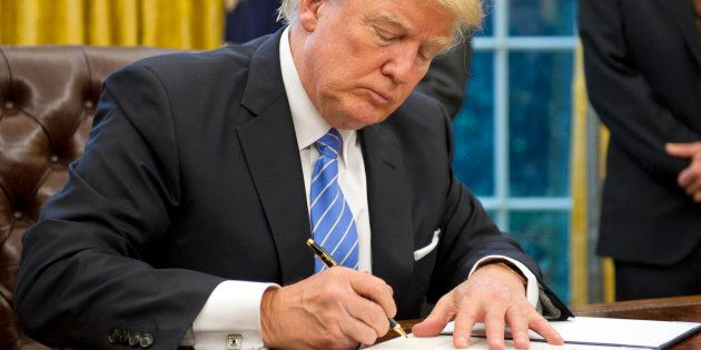 WASHINGTON, DC - JANUARY 23:  (AFP OUT) U.S. President Donald Trump signs the last of three Executive Orders in the Oval Office of the White House in Washington, DC on Monday, January 23, 2017.  These concerned the withdrawal of the United States from the Trans-Pacific Partnership (TPP), a US Government hiring freeze for all departments but the military, and 'Mexico City' which bans federal funding of abortions overseas. (Photo by Ron Sachs - Pool/Getty Images)