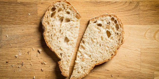 two slices of bread arranged in a heart shape on chopping block