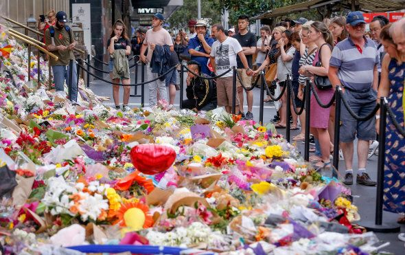 People pay their respects at a a tribute in Bourke St