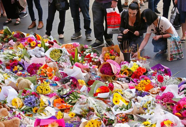 People look at floral tributes at Bourke St Mall for victims of the Bourke Street Mall