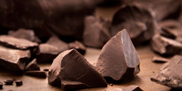 Pieces of dark chocolate spread out on a wooden background.