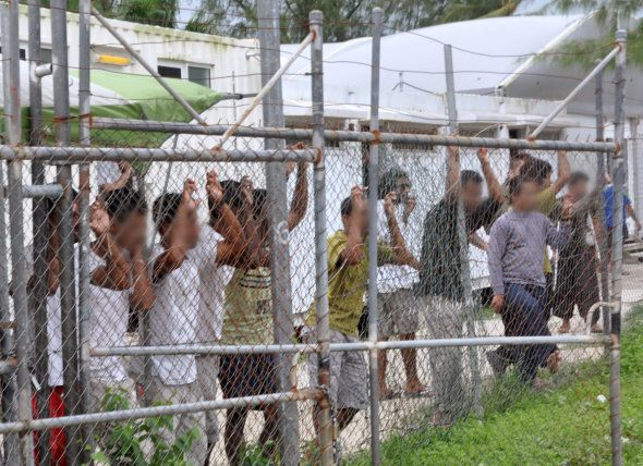 Asylum-seekers look through a fence at the Manus Island detention centre in March