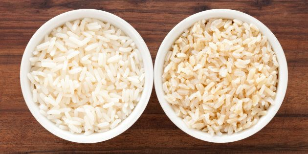 Top view of two bowls containing white and brown boiled rice