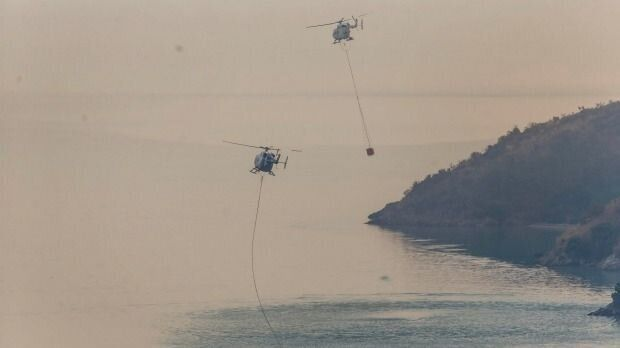 Helicopters fill buckets from Lyttelton Harbour