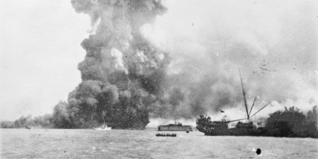 The SS Neptuna explodes at Stokes Hill Wharf, sending a column of debris and smoke hundreds of metres...