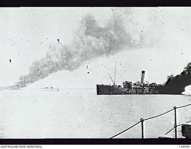 The SS Zealandia, an ammunition ship, on fire in the harbour after bing bombed during the air raid. on...