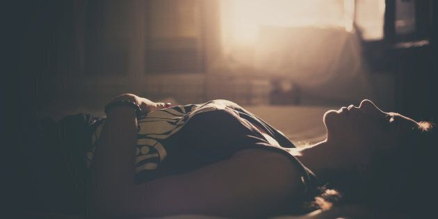 Sad girl in bed, backlit scene. Desaturated image.