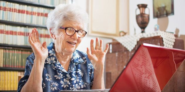 Surprised senior woman sitting in front of laptop at