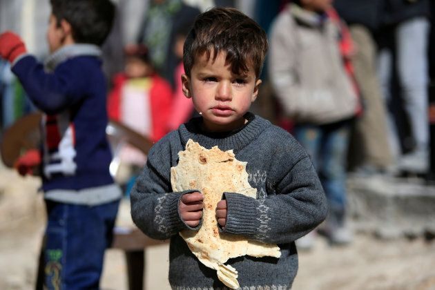 A displaced boy carries bread at a shelter in Jibreen, on the outskirts of Aleppo, Syria February 1, 2017.