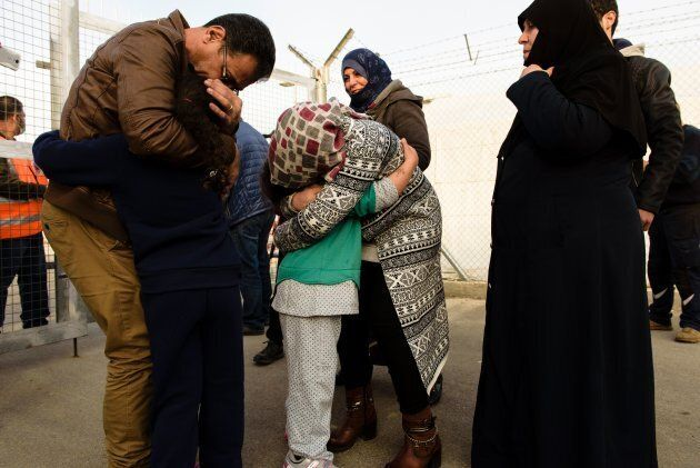 Refugees, who are members of the same family and were seperated due to the conflict in their countries, hug as they are reunited at the Kokkinotrimithia refugee camp, some 20 kilometres outside the Cypriot capital Nicosia, on February 4, 2017.