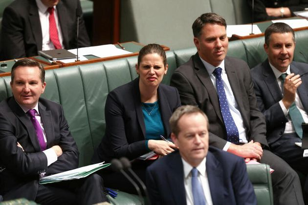 Shadow Education Minister Kate Ellis listens as Prime Minister Tony Abbott speaks during Question Time...