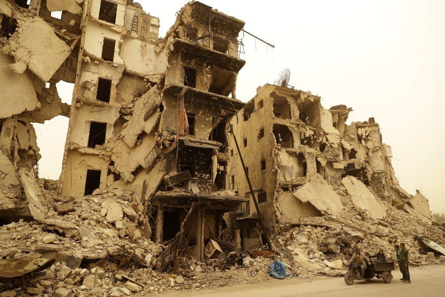 A Syrian man drives his vehicle past destruction in the once rebel-held Aghiour neighbourhood in Aleppo...