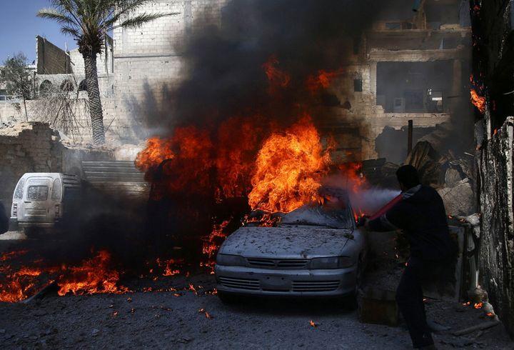 A man tries to put out a fire at a site hit by airstrikes in the rebel held besieged Douma neighbourhood of Damascus, Syria, February 26, 2017