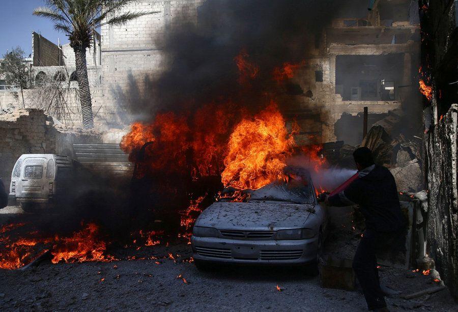 A man tries to put out a fire at a site hit by airstrikes in the rebel held besieged Douma neighbourhood...