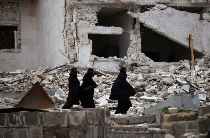 Women walk near damaged buildings in the northern Syrian city of al-Bab, Syria March 13, 2017.