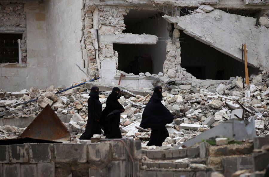 Women walk near damaged buildings in the northern Syrian city of al-Bab, Syria March 13,