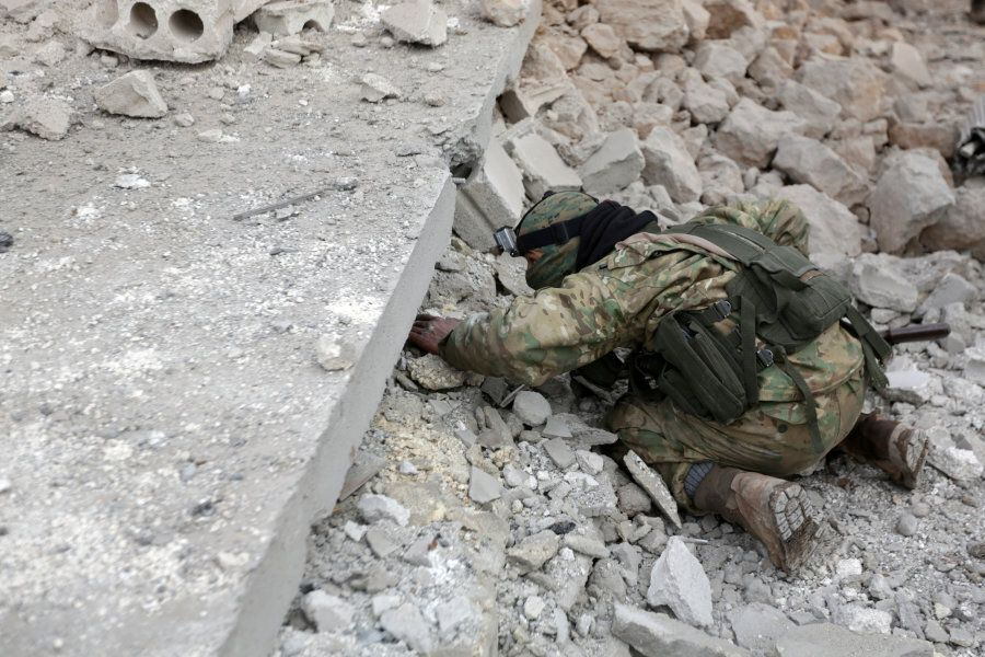 A rebel fighter looks for survivors under rubble of a damaged building after a car bomb explosion in...