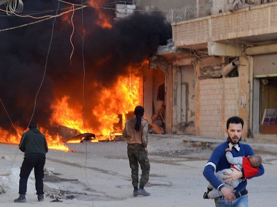 People leave the impact site after Assad Regime's airstrike over civilians in residential areas of Ariha...