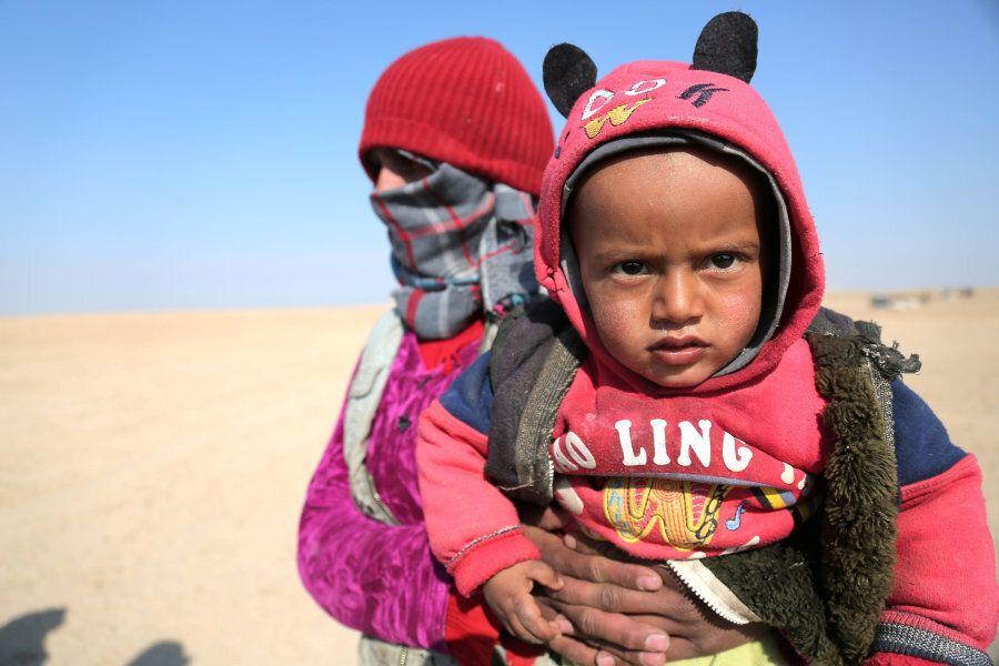 An internally displaced Syrian woman who fled Raqqa city carries a child in northern Raqqa province,...