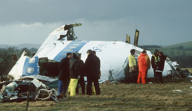 Emergency service workers are seen next to the wreckage of Pan Am flight 103, in a farmer's field east...