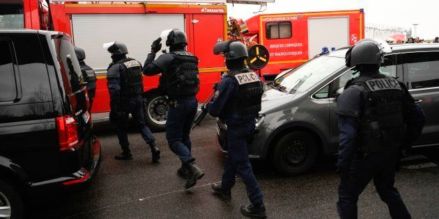 French policemen and firefighters secure the area at Paris' Orly airport on March 18, 2017 following the shooting of a man by French security forces.Security forces at Paris' Orly airport shot dead a man who took a weapon from a soldier, the interior ministry said. Witnesses said the airport was evacuated following the shooting at around 8:30am (0730GMT). The man fled into a shop at the airport before he was shot dead, an interior ministry spokesman told AFP. He said there were no people were wounded in the incident. / AFP PHOTO / CHRISTOPHE SIMON        (Photo credit should read CHRISTOPHE SIMON/AFP/Getty Images)