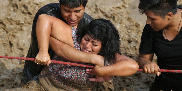 Two men help a woman cross a flooded street after a river overflowed, sending torrents of mud and water...