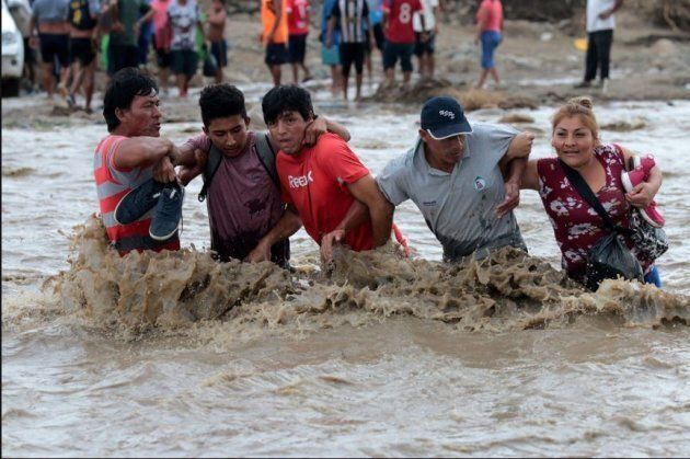 Residents link arms as they attempt to cross the Viru river after a bridge collapsed following a massive...
