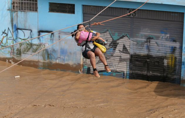A woman and a child are evacuated by zip line after the Huaycoloro river flooded, sending torrents of...