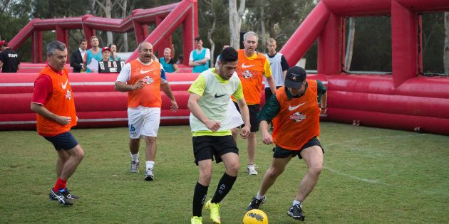 Minister for Health and Sport, Greg Hunt, (centre, in hat) plays against the Street Socceroos team at...