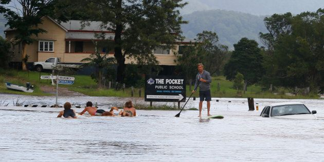 Locals paddle down the main street of Billinudgel in