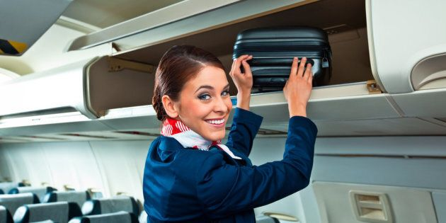 Beautiful flight attendant putting a suitcase in an overhead compartment in an airplane and smiling at the camera.