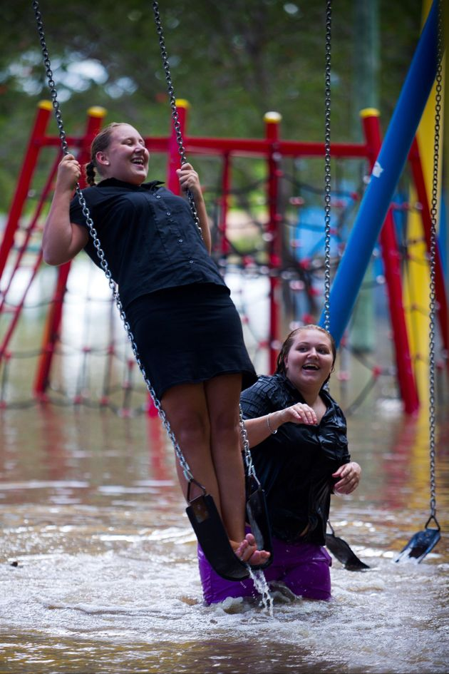 Crystal Warner (L) and Sharnia Johns (R) play on playground equipment as floodwaters caused by Cyclone...