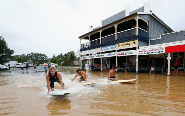 BILLINUDGEL, AUSTRALIA - MARCH 31:  Local residents surf down the main street on March 31, 2017 in Billinudgel, Australia. Heavy rain has caused flash flooding in south east Queensland and Northern New South Wales as as ex-cyclone Debbie makes its way south across the country. Category 4 Cyclone Debbie hit Northern Queensland on Tuesday, causing widespread damage.  (Photo by Jason O'Brien/Getty Images)