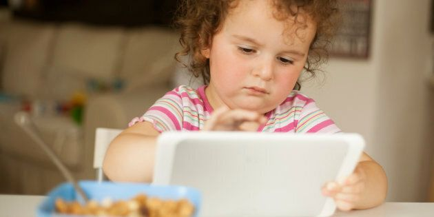 cute little girl eating cornflakes and playing on digital