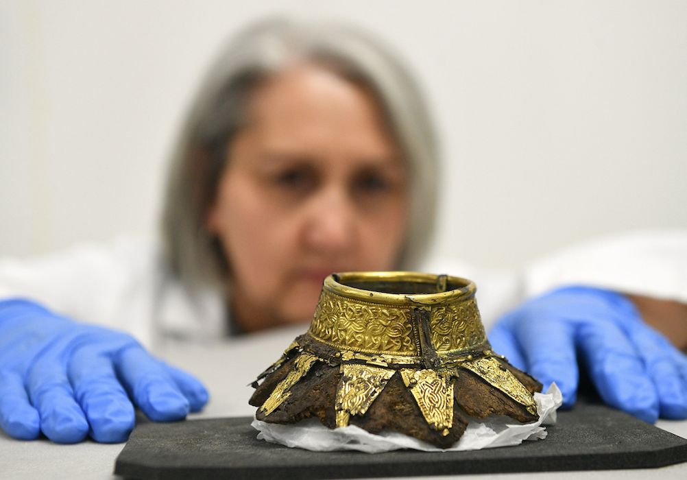 Conservator Claire Reed inspects the remains of a wooden drinking vessel with a decorated gold neck found inside the chamber (PA)