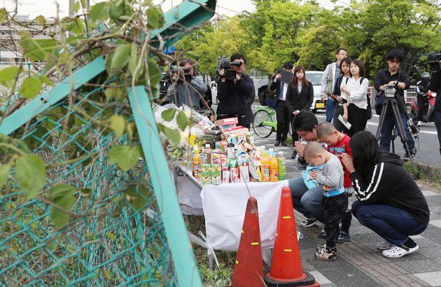 保育園児らの列に車が突っ込んだ事故現場で手を合わせる人たち=5月9日午前、大津市