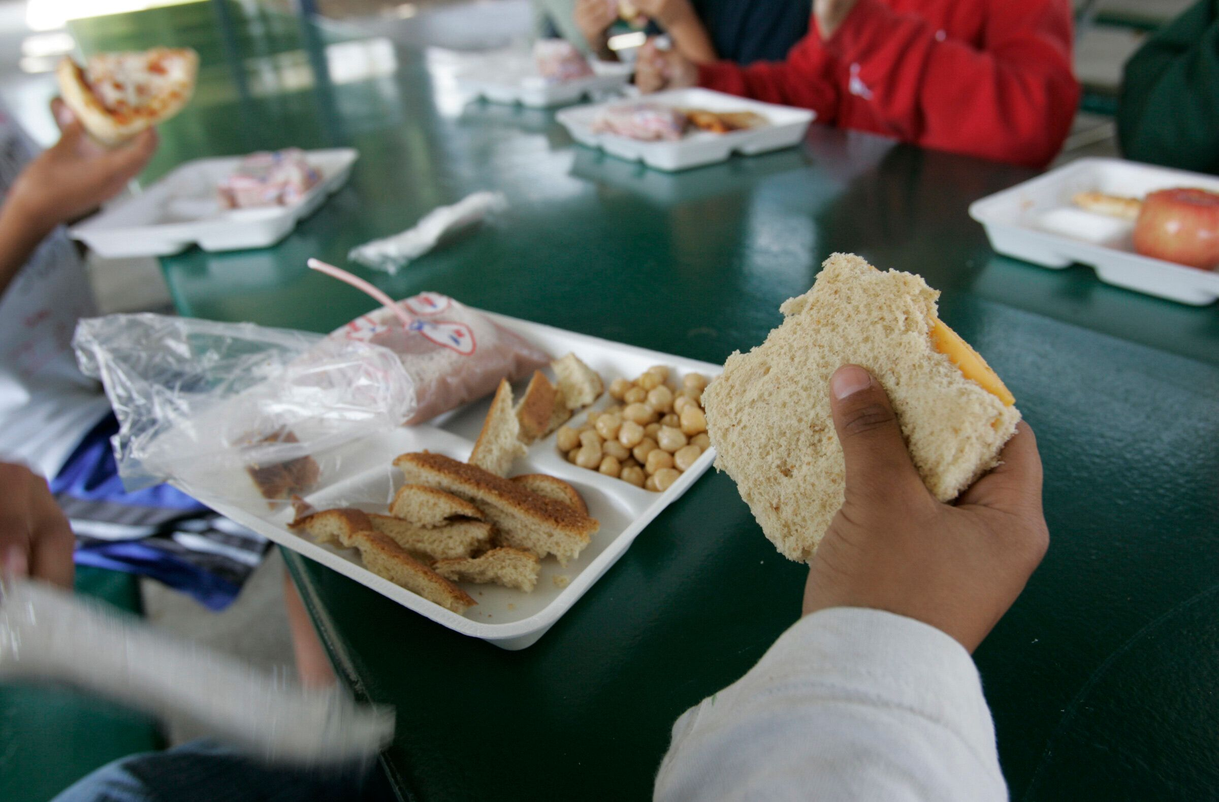 June 12, 2007. Chula Vista, CA. A 4th grade boy stripped the crust from his plain cheese sandwich. He added beans to his plate and chose chocolate milk to go with the meal. Students at Hilltop Elementary School whose parents are behind on school lunch payments can only choose a cheese or ham sandwich. They may add condiments and lettuce to the sandwich and get a drink and fruit but can't select the popular items like pizza or peanut butter & jelly sandwiches. – Since the limited choice was implemented, the Chula Vista Elementary School District has cut parental non–payments dramatically.  (Photo by Don Bartletti/Los Angeles Times via Getty Images)