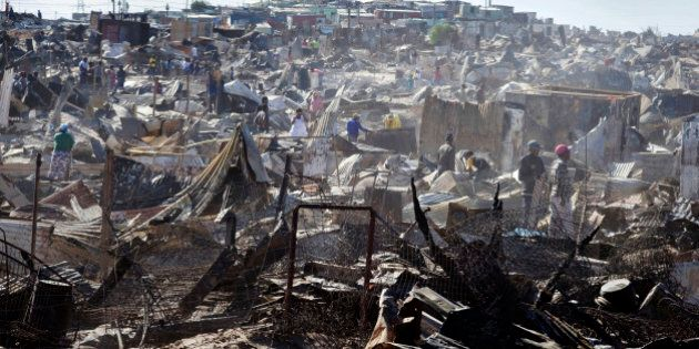 People look through the remains of burnt homes after a fire raged through the BM Informal Settlement,...