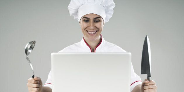 happy woman chef looking at the laptop computer with knife and ladle in her