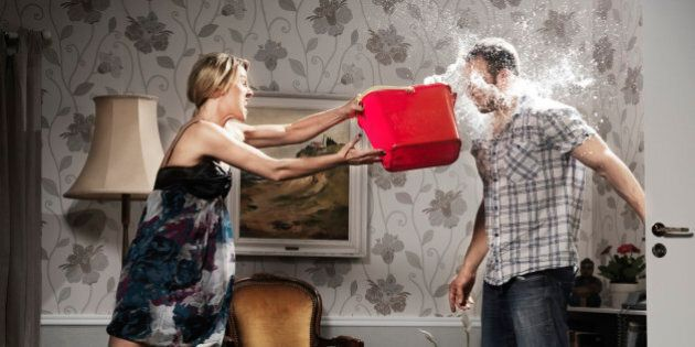young woman thowing a bucket of water at her partner, in the living room