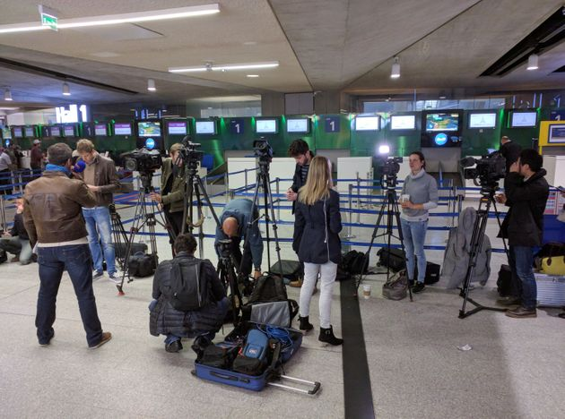 Reporters gather at Charles de Gaulle Airport outside of