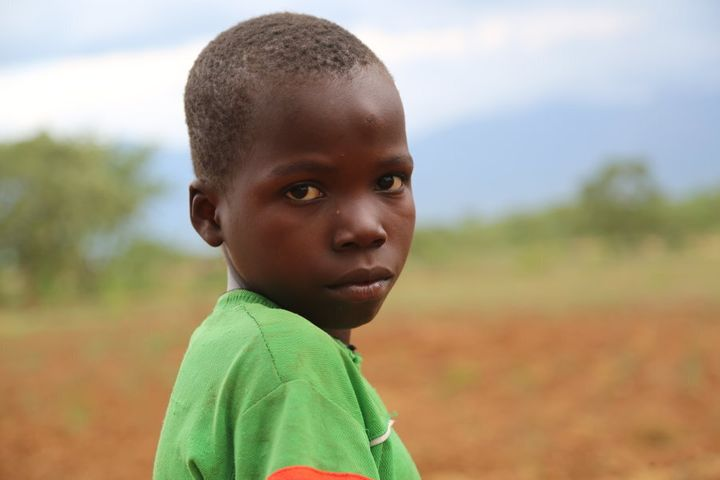 Precious Lameck, 13, pictured in his family's dried up garden.