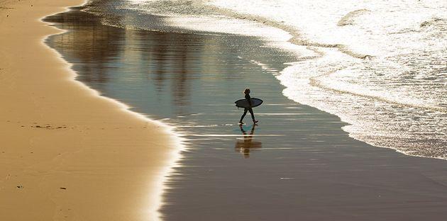 A surfer dives in despite storm debris warnings at Collaroy