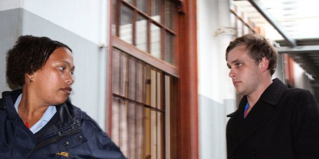 Henri van Breda, right, is led by a South African police woman as he arrives at the Stellenbosch magistrate...