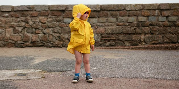Young boy wearing a yellow jacket at the Engliash seaside, on a windy