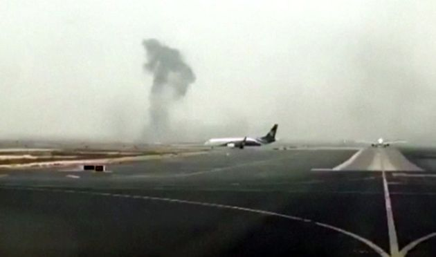 Smoke rises in the distance from the crash-landed Emirates