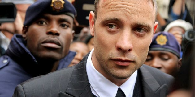 Olympic and Paralympic track star Oscar Pistorius leaves court after appearing for the 2013 killing of...