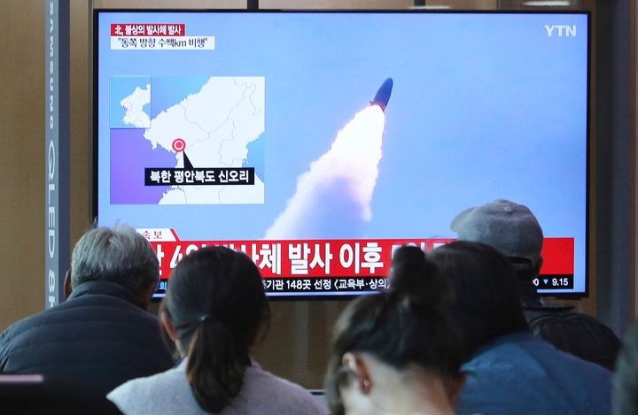 People watch a TV showing file footage of North Korea's missile launch during a news program at the Seoul Railway Station in