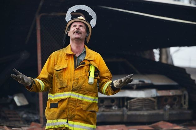 A Country Fire Service volunteer revels in the rain after bushfires in the Adelaide Hills in January,